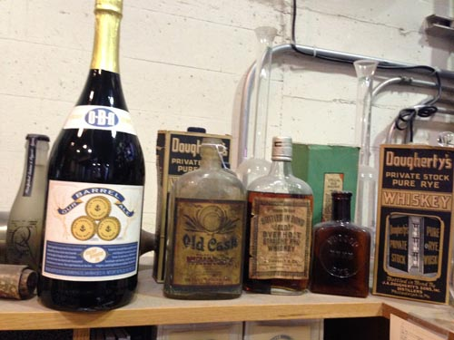 A magnum of OBA and several prohibition-era whiskey bottles.